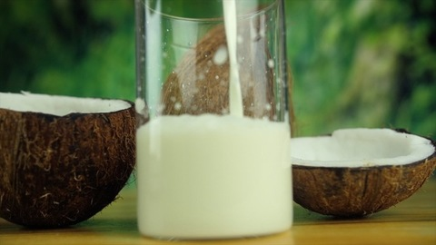 Closeup shot of pouring coconut milk in a transparent glass - vegan food concept