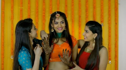 Friends posing for pictures with an Indian bride-to-be during a traditional function