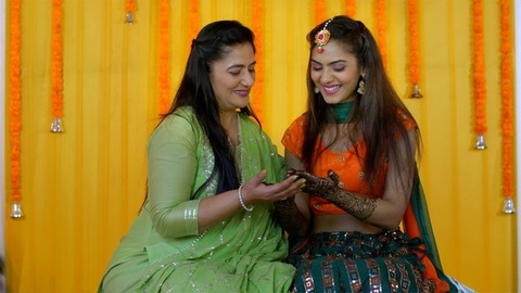 Mehendi ceremony - Indian wedding. Mother giving blessings to her daughter. Indian bride