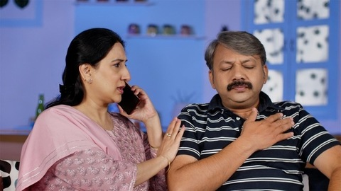 Indian woman making a phone call while sitting with her husband at home