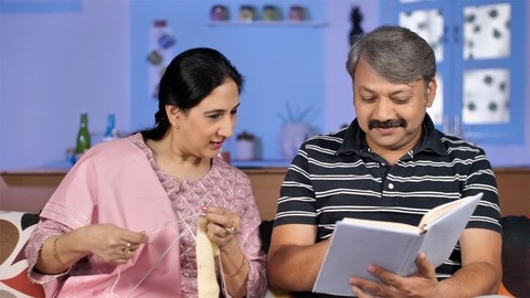 Indian male with grey hair showing interesting things to the wife while reading a storybook