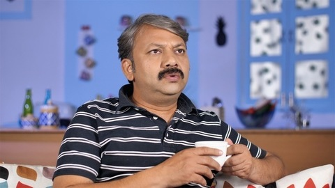 Middle-aged Indian man thinking about his future while drinking tea at his home