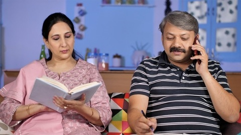 Indian lady flipping the pages of a storybook while her husband busy on mobile
