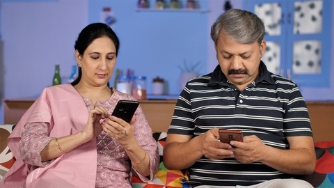 Two mature adults browsing their mobile while sitting together on the sofa