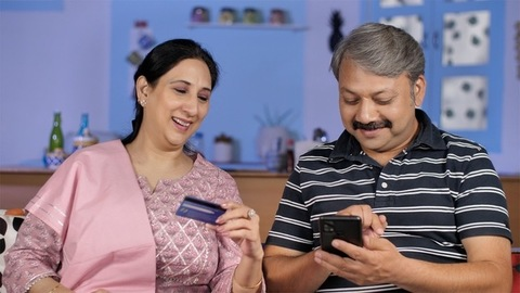 Attractive housewife helping her husband to put credit / debit card details for online shipping
