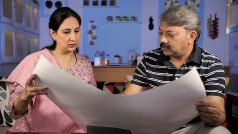 Two middle-aged Indian people planning the interior design of their new house