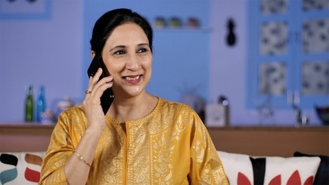 Portrait of a happy Indian lady talking on her smartphone in her living room