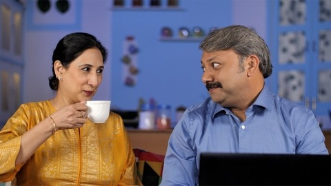 Caring wife brings two cups of tea while her husband busy doing official work