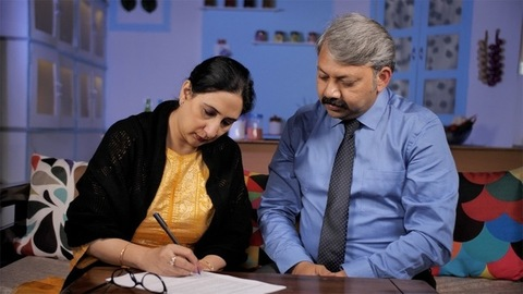 Indian insurance agent helping his client while filling the insurance form