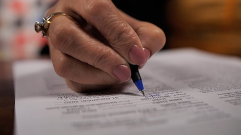 Female hand signing a contract paper by a ball pen - signature on an agreement
