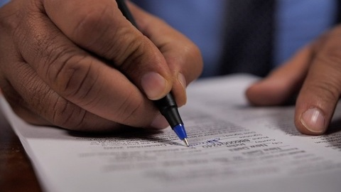 Male signing an important contract paper for official work