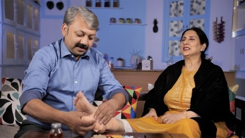 Caring Indian husband putting a cloth / crepe bandage on his injured wife's feet