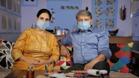 A mature couple wearing surgical masks at home - protection against Coronavirus