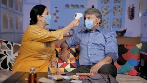 An Indian couple wearing medical masks at home - protection against COVID-19