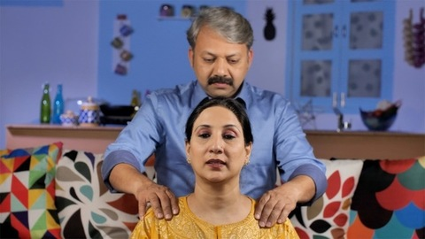 Matured male massaging the shoulders of his tired wife - comforting concept
