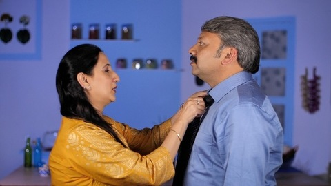Shot of a mature Indian wife helping her husband to wear a necktie