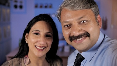Modern Indian couple cheerfully making a video conference call - technology concept