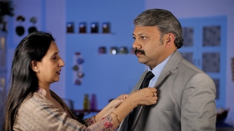 Modern Indian woman helping her businessman husband to wear a coat while getting ready - Happily Married