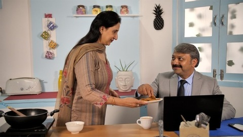 Caring Indian housewife giving tea and biscuits to her husband - loving family