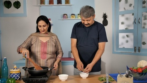 Caring Indian husband helping his wife in the kitchen to make a tasty dish