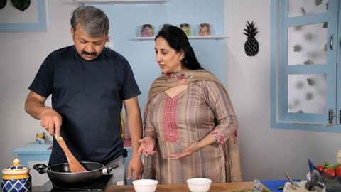 Grey-haired male cooking in the kitchen while the wife is happily instructing him