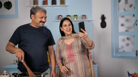 An attractive housewife happily talking and waving on a video call using her smartphone