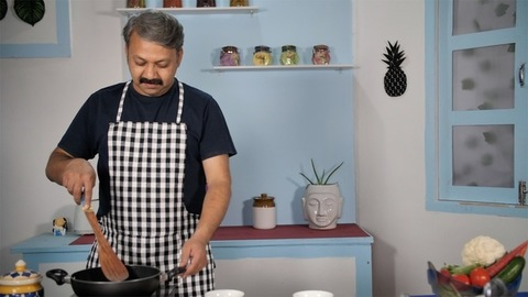 Modern Indian male cooking a tasty dish in the kitchen - homestyle cooking