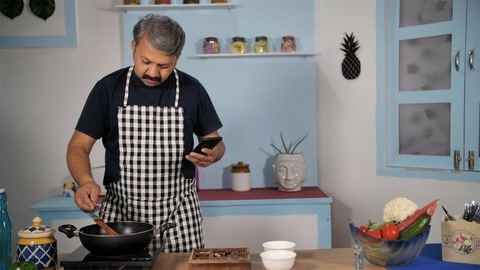 Middle-aged husband alone at home checking recipes on his mobile to cook meals - Indian kitchen