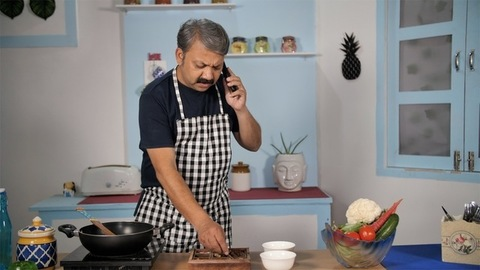 Professional Indian male cook adding spices to his food - home-style cooking in Indian kitchen