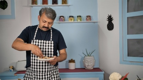 A grey-haired cook garnishing his dish with dry fruits - cooking in Indian kitchen
