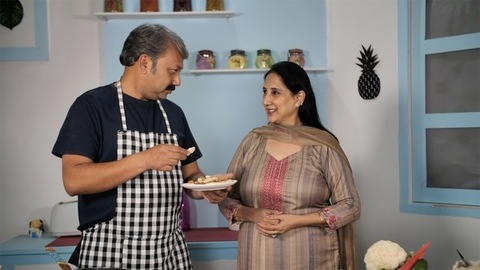 Middle-aged wife tasting and appreciating the food made by her husband