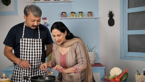 Happy male watching his wife tasting food from the pan - cooking concept