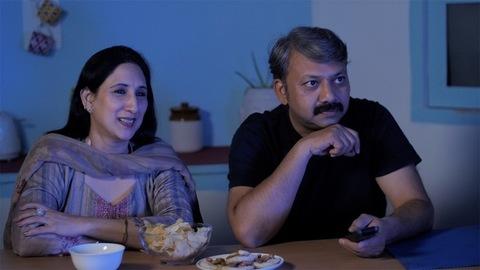 Mature couple enjoying their favorite TV program at home - leisure time