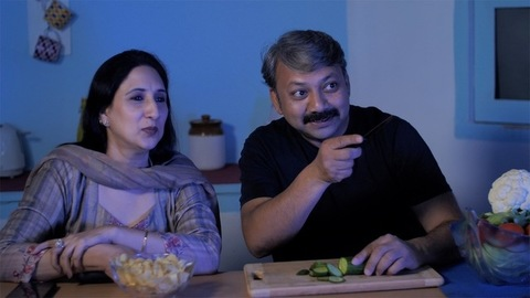 Mature female eating snacks and surfing TV channels sitting with her husband
