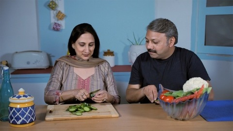 Middle-aged urban wife chopping fresh and healthy salad - health consciousness