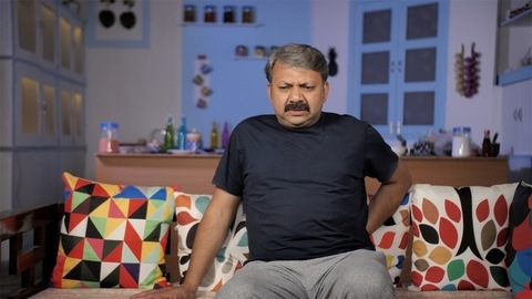 Indian male suffering from severe backache while getting up from the sofa