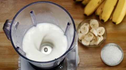 Banana smoothie / banana shake with milk beating in a blender - healthy and refreshing drink