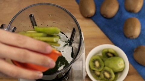 Making a kiwi fruit smoothie in a blender - refreshing drink for healthy living