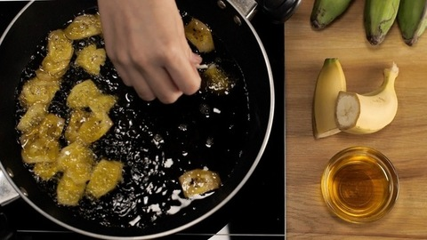 Female hand putting pieces of banana in hot oil for frying - food and nutrition. Banana chips making