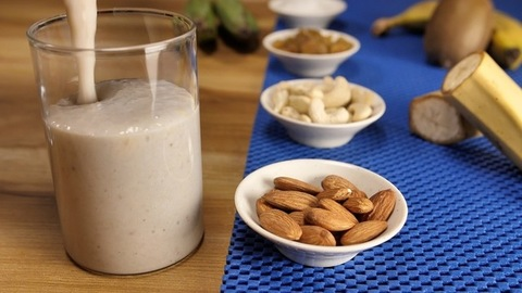 Ripe banana milkshake with various dry fruits pouring into a transparent glass - Healthy protein shake