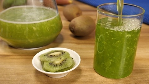 Refreshing green kiwi fruit juice pouring into a transparent glass - cool summer drink