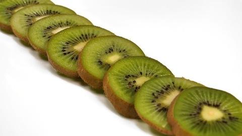 Citrus kiwi fruit slices against a white background - healthy food