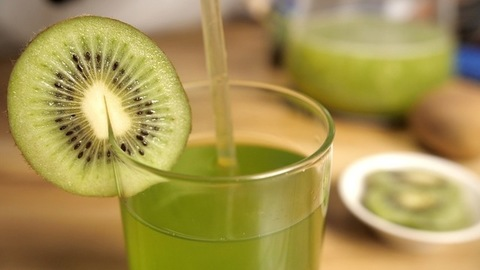 Transparent straw dipped in a glass of kiwi fruit juice - a tasty drink for healthy diet