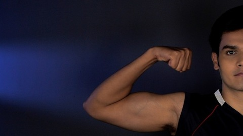 Half face of healthy Indian male showing his biceps against a dark background