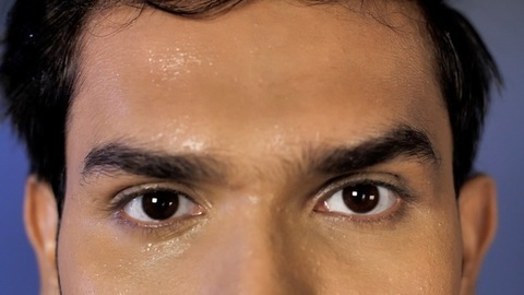 Extreme closeup of male's eyes and forehead with droplets of sweat - active lifestyle