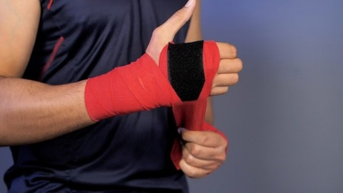 Muscular Indian man wrapping red boxing wrap bandage while getting ready for a training