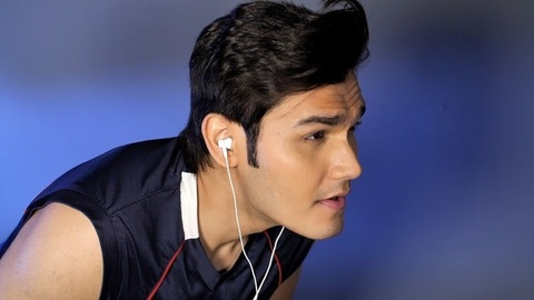 Side view of an urban Indian youngster with earphones enjoying music indoors