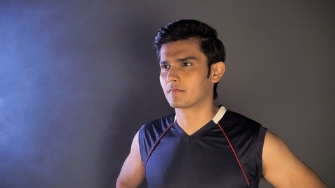 Portrait of a young athlete standing against a dark background - fitness activity