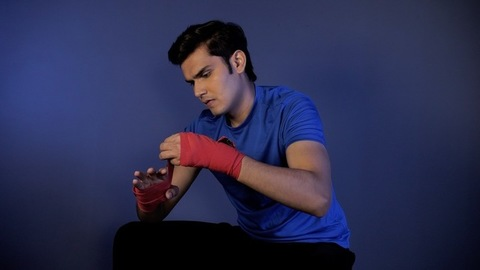 Shot of a strong Indian youth wearing red wrap sports bandage on hands