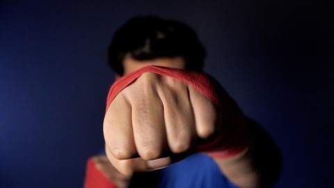 Determined Indian youth practicing boxing punches against a dark background
